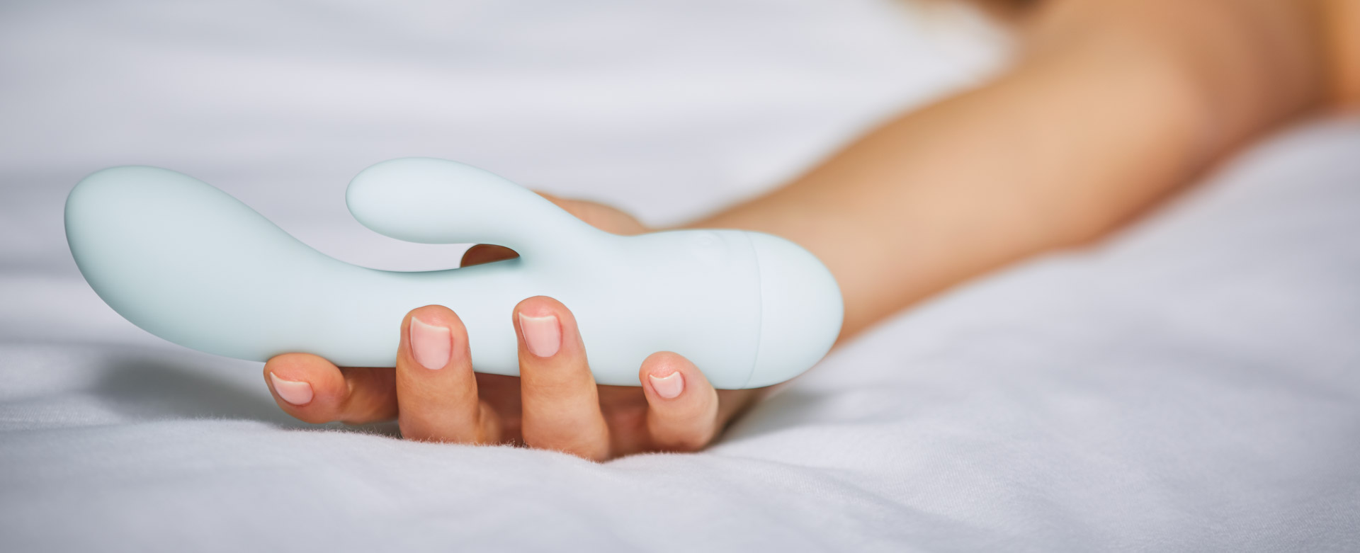 woman holding rabbit vibrator lying on bed