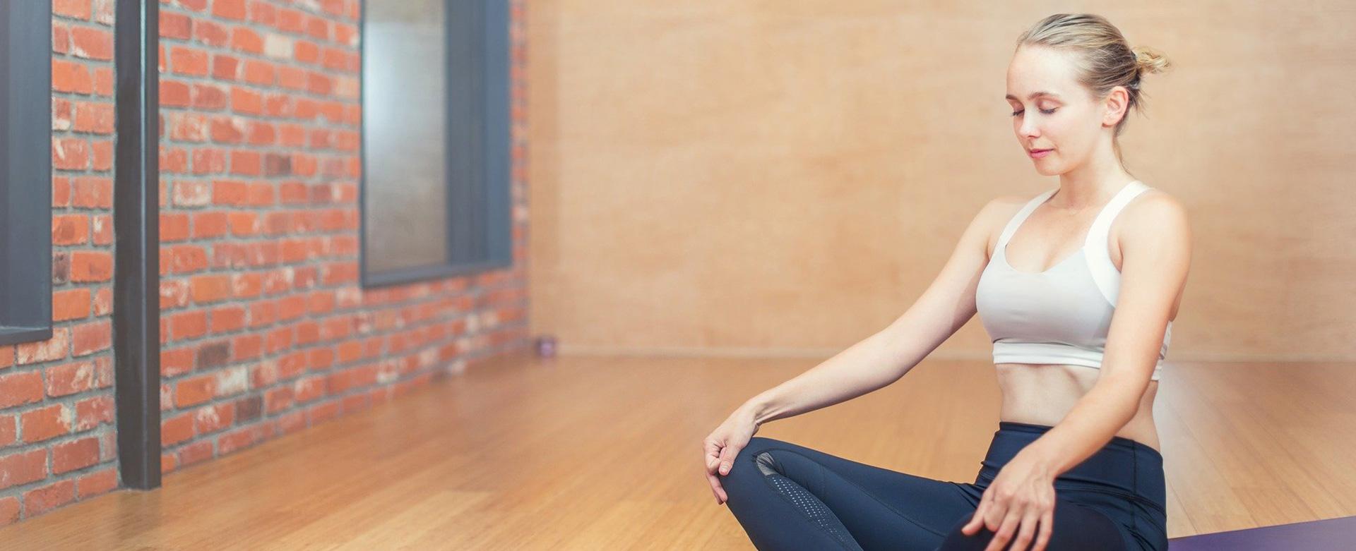 Woman relaxing with legs crossed practising kegel exercises