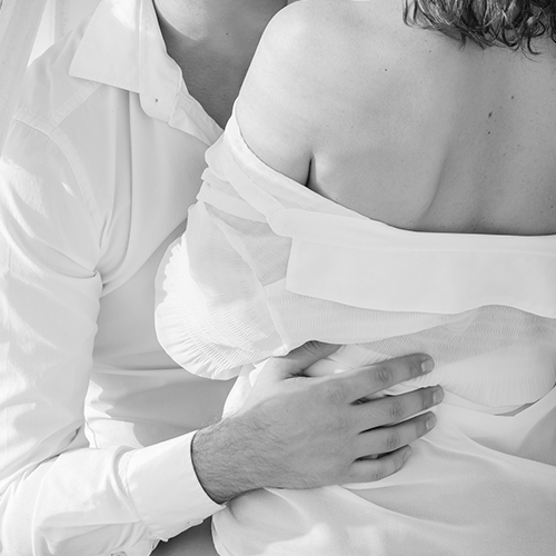 Couple standing closely in loose white shirts, the man has his hand on the woman's waist