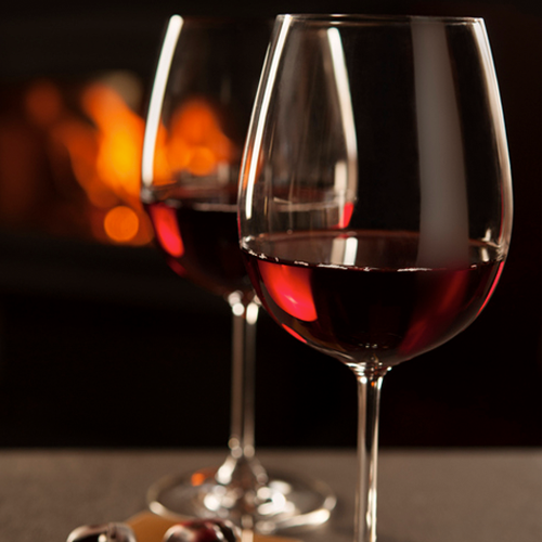 Two wine glasses half full with red wine in front of a fire