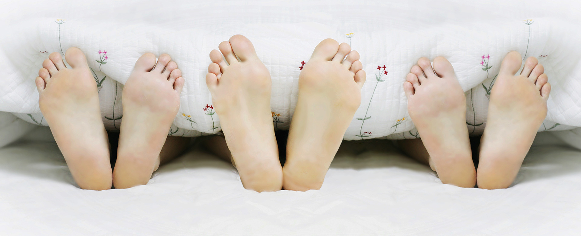 Three pairs of feet in a bed