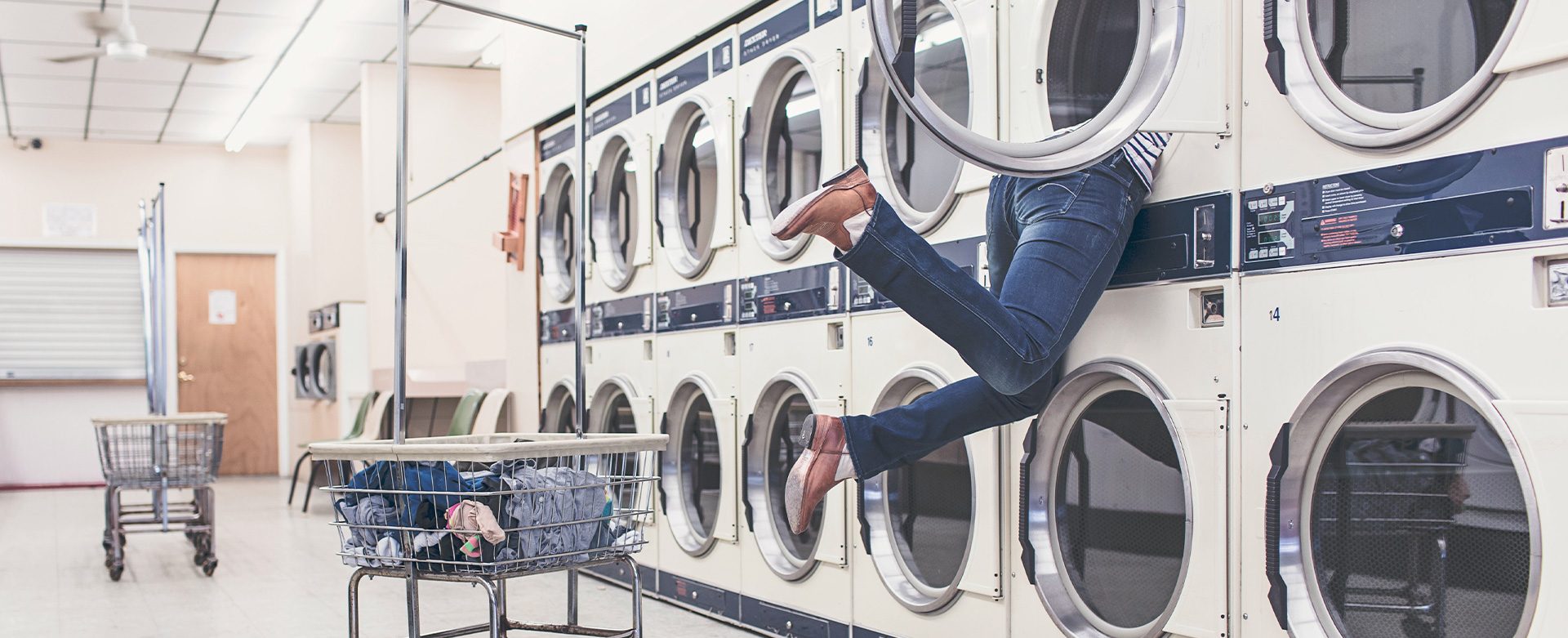 A pair of legs hanging out a washing machine in a laundrette