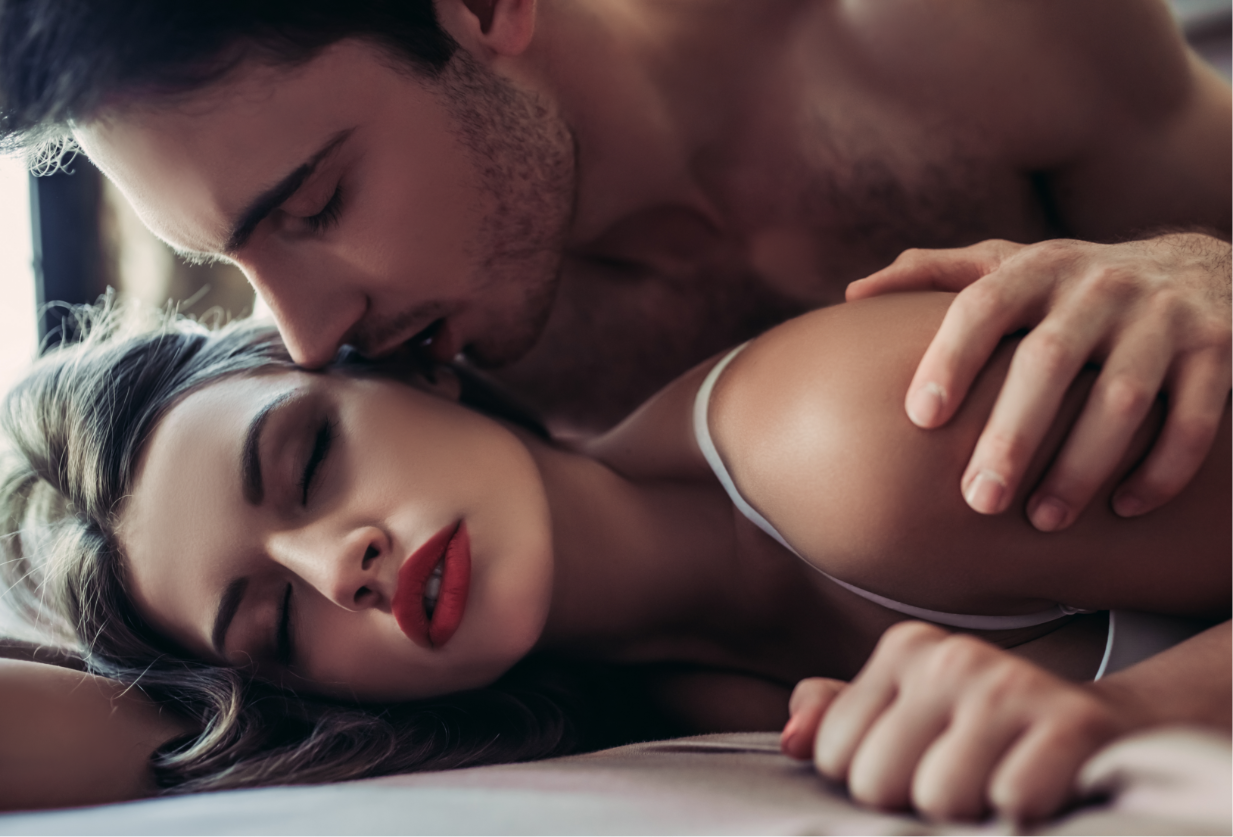 Man leans over women to kiss her cheek whilst lying on a bed